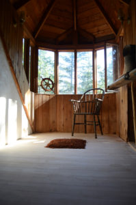 """Untitled with chair: an installation of fir seeds and sunlight, made by Andrew Miguel Fuller while in residency at the Alchemy Art Center. Sculptural art work by AM """"Andy"""" Fuller."""